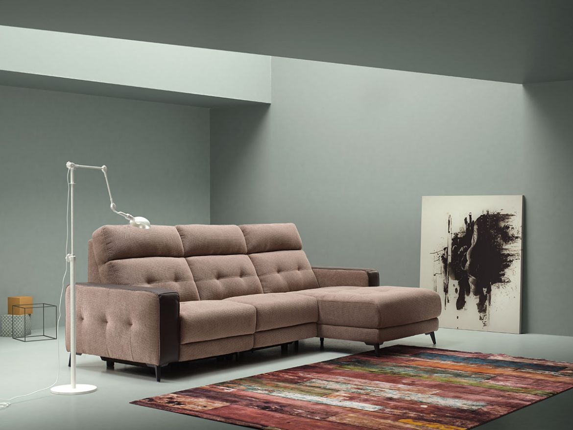 Chaise longue upholstered in brown microfiber with light touches of salmon, dark brown leather arms. The model is presented in a room with beige walls, large multicolored carpet and abstract Expressionism style painting supported on the wall.