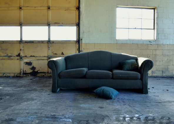 Disused sofa located in a dirty ship. It has a cushion on the floor.